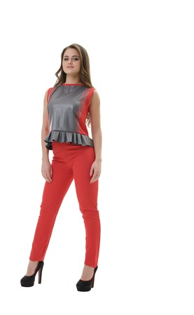 Young pretty long haired brunette in red pants, sleeveless blouse with Basques and high heels posing in studio shot from the front Stock Photo