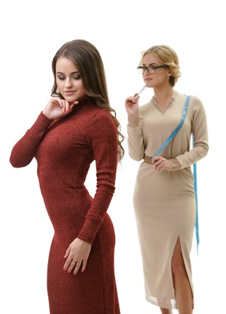 winy: Young sexy dressmaker in slinky beige dress takes measurements of her cute slim long haired client in sexual knitted winy gown studio shot