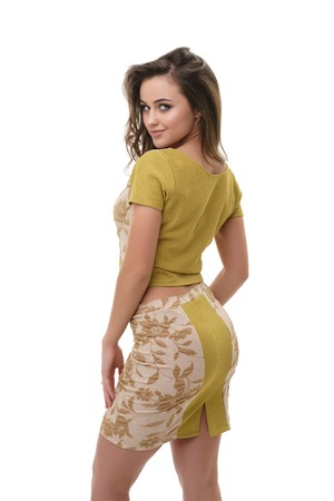 Sexy pretty long haired brunette in slinky printed mustard blouse and mini skirt posing flirty in studio half-turned