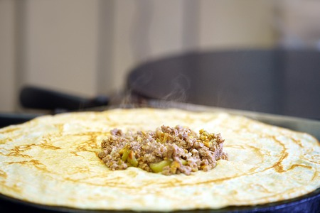 forcemeat: Pancake stuffed by forcemeat with greenery frying in oil on pan in a cafe