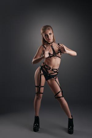 mujeres eroticas: Mujer atractiva joven que presenta en los cinturones de cuero negro