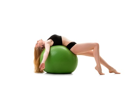 Female gymnast lying on back on green big fitball Stock Photo