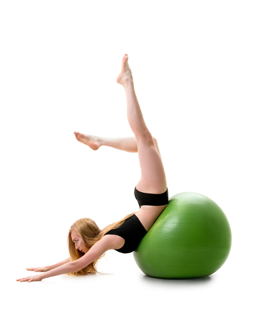 Female gymnast poses on stomack on green fitball