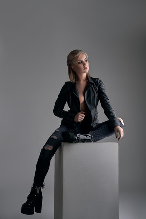 glam rock: Model in leaher jaket and boots posing at studio