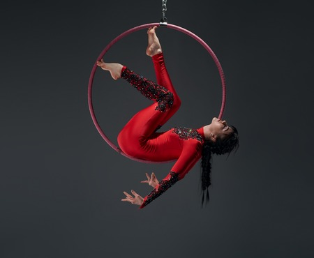 silks: Young slim gymnast with red hoop artistic portrait