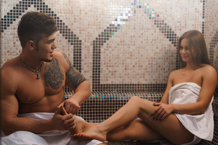 sauna nackt: Young man making sexy girl foot massage in sauna