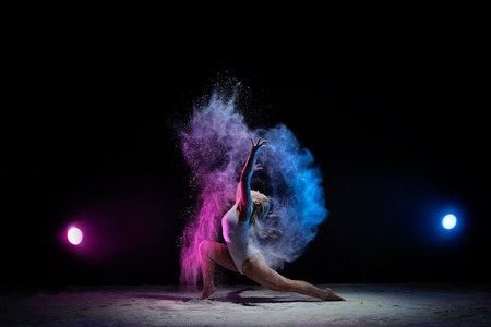 Young girl posing in color dust cloud in studio Stock Photo
