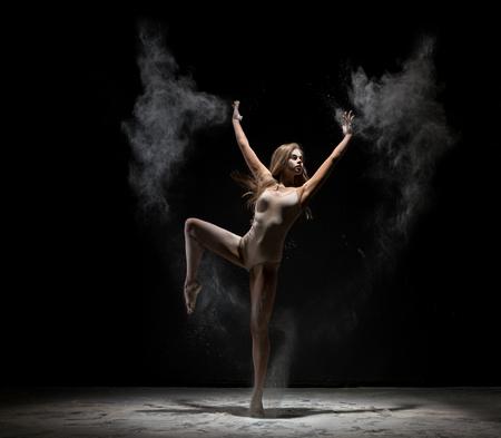 gracefully: Beautiful blonde dancing in cloud of white dust