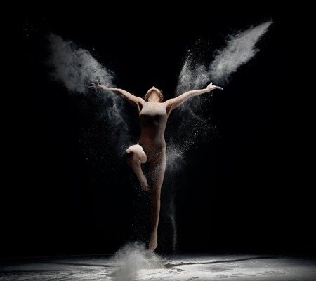 Slender girl dancing in white powder cloud