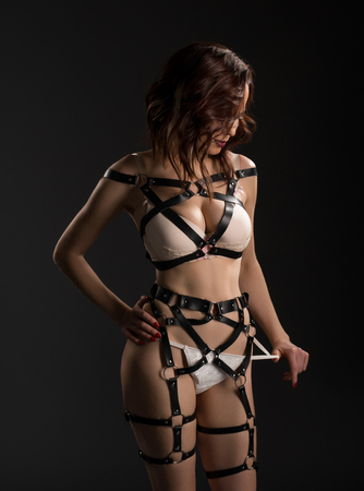 erotic woman: Model in beige lingerie and leather belts