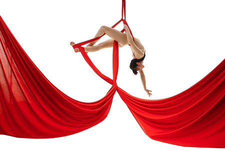 Young girl exercises on red aerial silks in studio