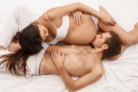 Man kissing belly of pregnant wife lying in bed Stock Photo