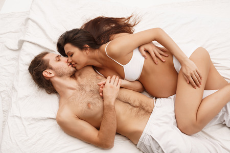 Pregnant young woman in bed kissing her husband