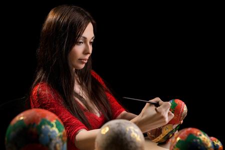 matrioshka: Pretty woman drawing patterns on matrioshka