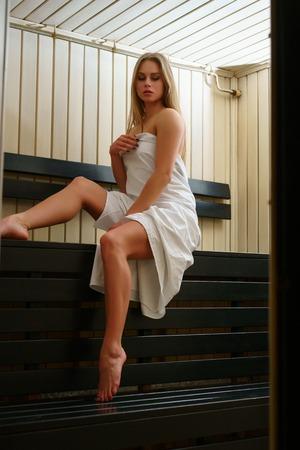 Herrliche Blondine im weißen Tuch in der Sauna eingewickelt