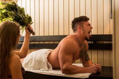 Junge sexy Paar ein Dampfbad mit Besen nehmen