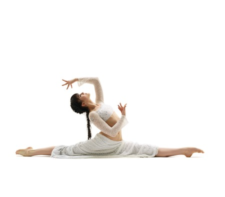 Young gymnast sitting in graceful split in studio