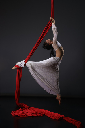 Young woman exercising on aerial cloth Stock Photo