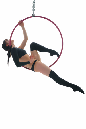 Young gymnast perfoming aerial exercise on hoop Stock Photo