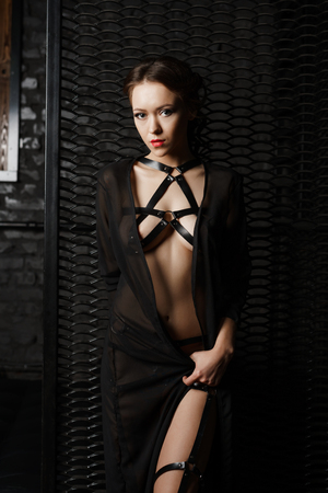 erotic woman: Sexy woman in black leather belts and silk gown