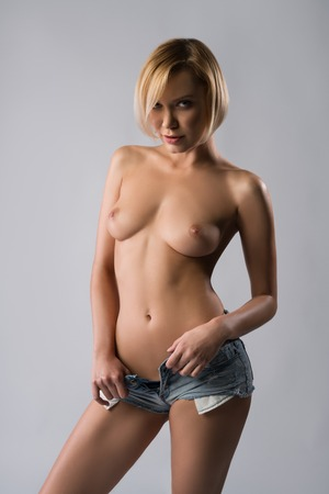 Topless sexy girl in denim shorts at studio