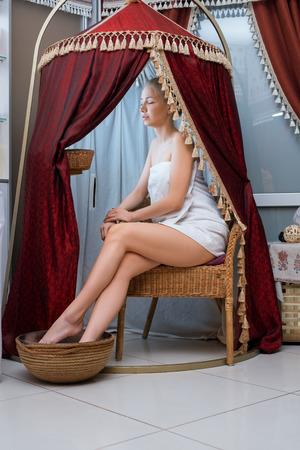 Hübsche Blondine im Spa-Salon sitzt in einem Festzelt