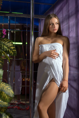 erotic woman: Young blonde wrapped in white towel in sauna Stock Photo