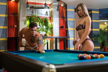 Junge sexy Paar spielt Billard in der Sauna