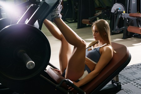 gracefully: Sexy blonde trainer posing in sports gym