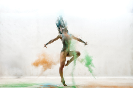 gracefully: Sexy girl in a cloud of color dust studio portrait