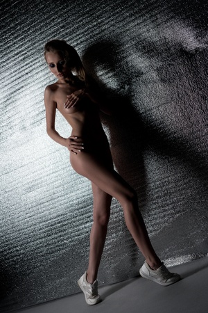 Young girl posing nude on silver backgroung photo
