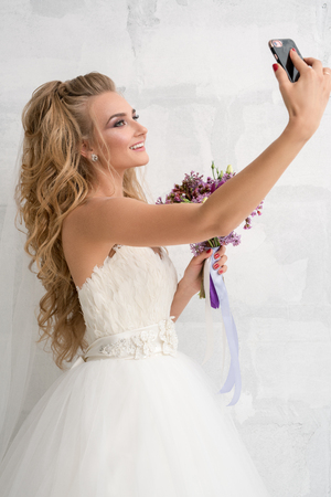 Young bride with bouquet in studio making selfie Stock Photo