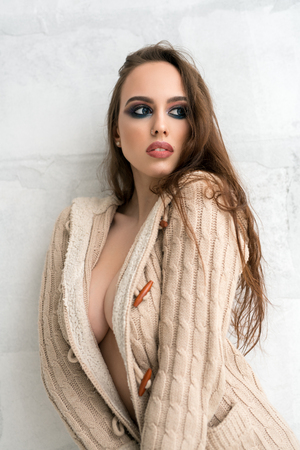 Sexy young girl in cardigan worn on naked body