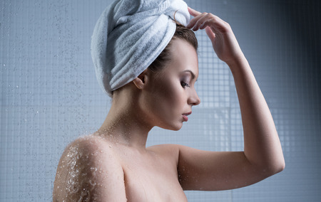 Girl with towel on her head and water drops around photo