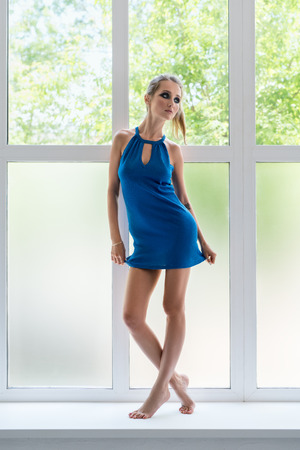 Slim blonde in nice summer dress on window sill photo