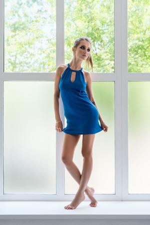 Slim blonde in nice summer dress on window sill Stock Photo