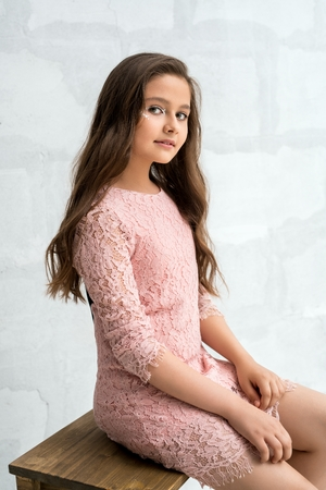 Teenaged girl in lace dress against brick wall
