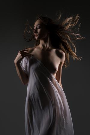 Slim brunette white cloth draped over her body
