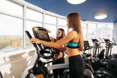 Slim girls on exercise bikes installing programme Stock Photo
