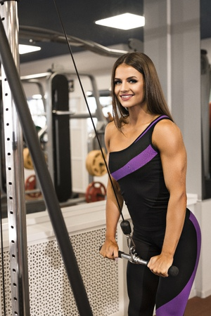 Sexy brunette working on simulator in a gym