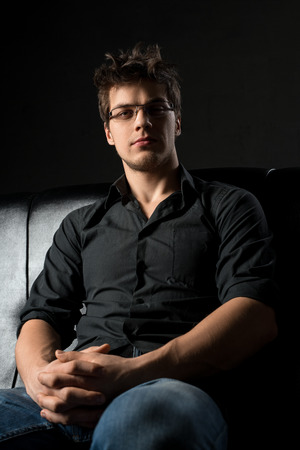 Young sexy man on leather sofa cropped portrait
