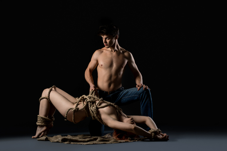 Shirtlesss man and nude girl tied with rope shot 免版税图像