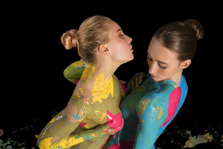Two nude girls with colorful bodyart cropped shot Standard-Bild