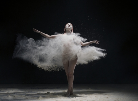 Woman dancing gracefully in dust cloud view Stock fotó