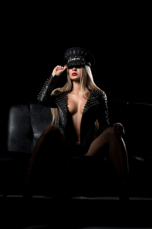 Sexy blonde topless in bdsm cap and leather jacket 스톡 콘텐츠