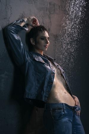 Brunette in wet jeanswear under water in the dark Stock Photo