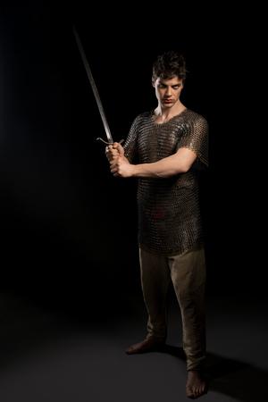 Sexy man in viking hauberg with sword in dark Stock Photo