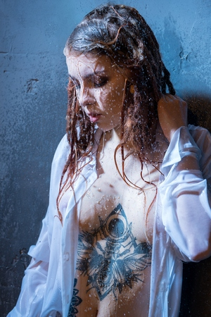 Young tattooed girl having shower portrait Stockfoto