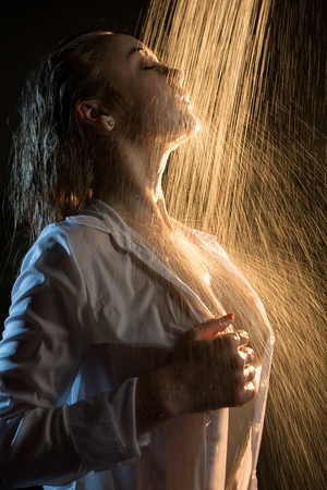 Young girl topless having shower in the dark Banque d'images