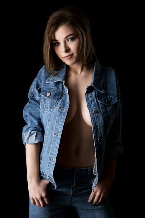 Pretty sexy girl in unbuttoned jeans jacket shot 스톡 콘텐츠